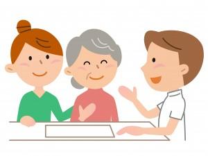 介護職員と会話するお年寄りとその家族